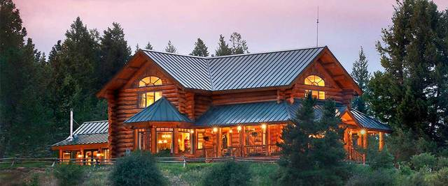 Log Home with pine trees surrounding